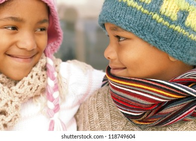 A moment of tenderness between two young siblings dressed in warm winter woollies as they sit close together smiling at one another