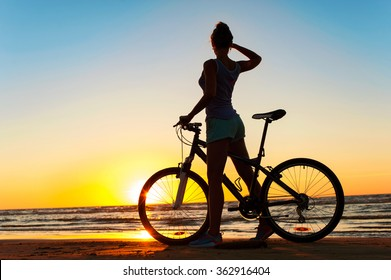 Moment in time. Young sporty woman cyclist silhouette contemplating the sunset on blue sky background on the beach. Summertime multicolored outdoors horizontal image.