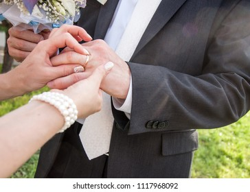 The moment of tying the wedding ring. Wedding rings, wedding day. Wedding couple. He put an engagement ring on her. A stylish bridegroom wearing a ring on the finger of his elegant bride