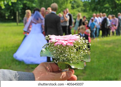 Moment in wedding, bride and bridegroom handshaking with wedding guests in background, flower in the foreground