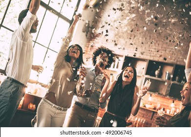 Moments of happiness. Cheerful young people throwing confetti and smiling while enjoying home party on the kitchen