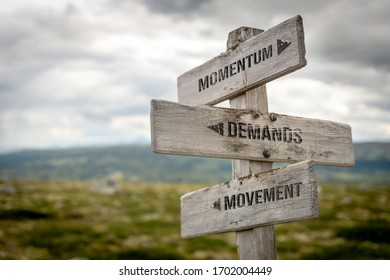 Momentum demands movement wooden sign outdoors in nature. Business and moving forward concept.