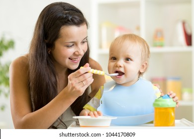 Mommy giving healthy food to her baby son on high chair in kitchen.