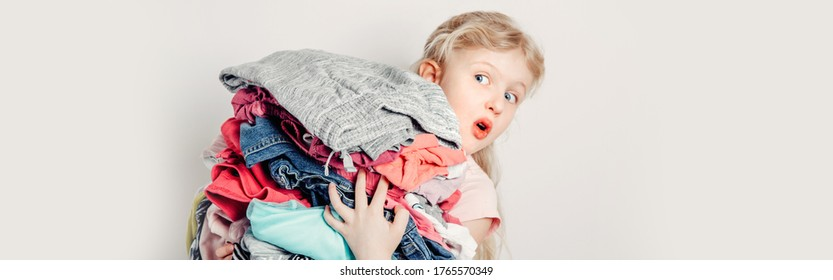 Mommy little helper. Funny cute girl child arranging organazing clothing. Kid holding messy stack pile of clothes things. Home chores housework. Web banner header for website.