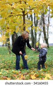 Mommy and little son the autumn park