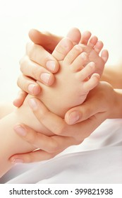 Mom's hands and baby feet. Loving hands of mother holding baby feet. Isolated on white background.