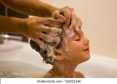Mom's hands washing little girly's head in the bathroom. The symbol of purity and hygiene education