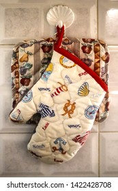 Moms kitchen - a potholder and an oven mitt hang from a plastic shell-shaped hanger on tile in a homey kitchen - closeup