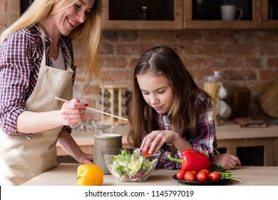 moms little helper. kid girl preparing salad for dinner. happy family cooking leisure and good parenting skills