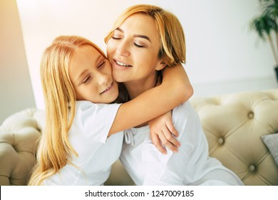Moms love. Happy beautiful mother and daughter spending time together, hugging and have a fun while sitting on the couch at home. Family concept