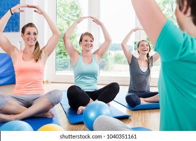 Moms in postnatal regression course doing yoga asana