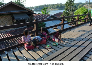 Mon children welcome tourists at the Mon Bridge,Sangkhlaburi, Kanchanaburi, Thailand on the afternoon of December 9, 2017.