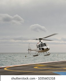 Monaco, Europe - January 2018:  Wide angle view of a helicopter coming in to land at the heliport with the sea and a cloudy sky in the background