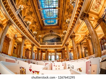 Monaco, France - October 10, 2018: Main hall of the luxury and famous Monte Carlo casino, with big player cards at the entrance and artistic design architecture of the ceiling