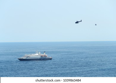 Monaco, Monte Carlo, 28 May 2017: The big cruise liner is near port Hercule, over it the helicopter flies by, small boats nearby float