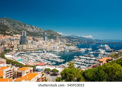 Monaco, Monte Carlo cityscape. Real estate architecture on mountain hill background. Many high-rise buildings in downtown area. Yachts moored at town quay In Sunny Summer Day