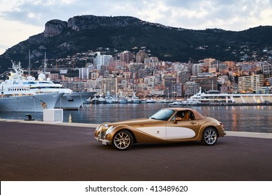 Monaco, Monte-Carlo, 06.04.2016: Exclusive car, retro type, gold color, standing on a pier in the port of Monaco, Hercules Port on background, Mitsuoka Himiko, cote dazur, sunset, night illumination