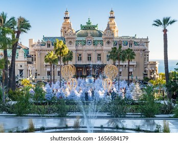 Monaco, Monte-Carlo, 25 December 2019: The square Casino Monte-Carlo at sunset, white Christmas trees, hotel the Paris, sunny day, Christmas decoration, tourists, fountain, new apartments, green lawn