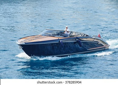 Monaco, Monte-Carlo, 4 sept 2015: Boat Riva Rivarama in the waters of the Port Hercules, dark color, black, shining in the sun, Monaco flag, operates the boat man in a white T-shirt and cap
