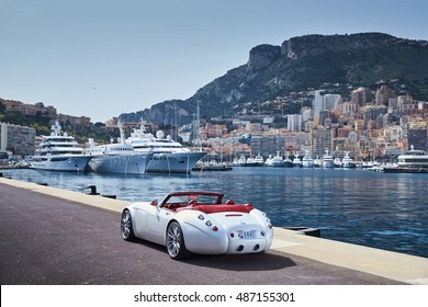 Monaco, Monte-Carlo, 6 April 2016: Exclusive expensive cars stand on the Monaco port pier overlooking the city and port Hercules, vintage cars Mitsuoka Himiko and Weissmann, cote dazur, sunny day