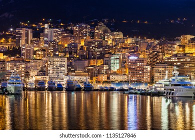 Monaco principality, city lights at night, modern apartment buildings with reflection in Mediterranean Sea, southern Europe