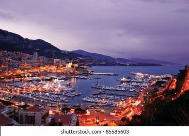 Monaco scenic at night including lavish yachts and the Monte Carlo skyline