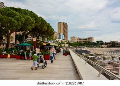 Monaco / Monaco — September 27, 2016: people walk on the beautiful sea promenade in Monaco near Larvotto beach, the only beach of the state