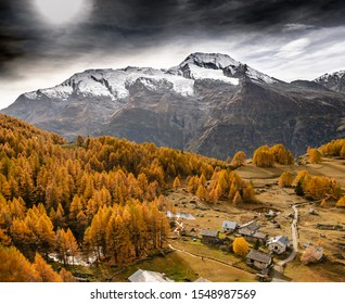 Monal village in Savoie, France, with orange fir trees and a mountain with glacier and snow