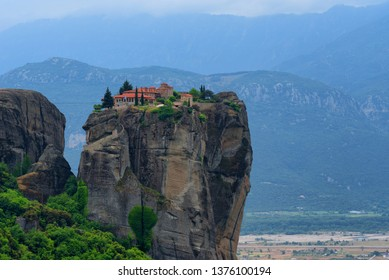Monastery Holy Trinity, Meteora, Greece. UNESCO world heritage Site. Epic spring landscape with temple at the edge of cliff at dramatic sky background.