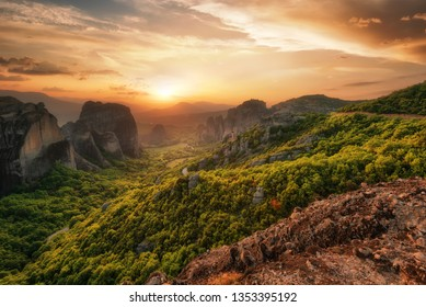 Monastery Meteora Greece. Stunning spring panoramic landscape at sunset. View at mountains and green forest against epic sky with clouds. UNESCO heritage list object. The Holly Monastery of Rousanou.