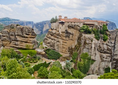 Monastery from Meteora-Greece with large green garden between tall and brown rocks