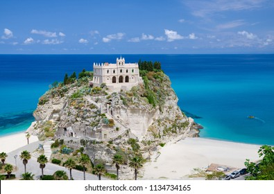 Monastery Sanctuary church of Santa Maria dell Isola on top of rock Tyrrhenian Sea and green palm trees, blue sky white clouds in summer clear day, Tropea town, Vibo Valentia, Calabria, Southern Italy