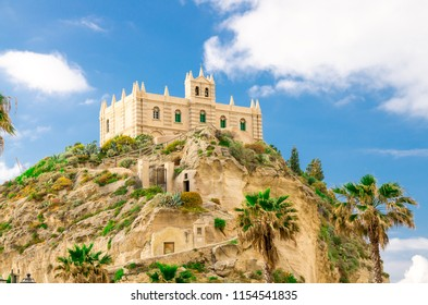 Monastery Sanctuary church of Santa Maria dell Isola on top of rock of Tyrrhenian Sea and green palm trees, blue sky with white clouds around, Tropea town, Vibo Valentia, Calabria, Southern Italy