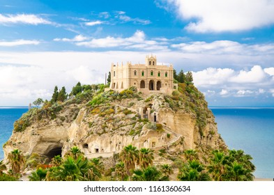 Monastery Sanctuary church Santa Maria dell Isola on top of rock of Tyrrhenian Sea and green palm trees, blue sky with white clouds around in sunny day, Tropea, Vibo Valentia, Calabria, Southern Italy