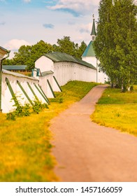 Monastery wall with road nearby runnig in meadow with trees. Summer landscape in Russia.