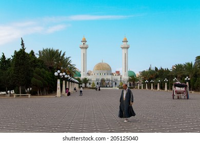 MONASTIR, TUNISIA - OCTOBER 08: Man in traditional arabic clothes walking in front of Habib Bourguiba Mausoleum in Monastir, Tunisia on October 08th, 2013
