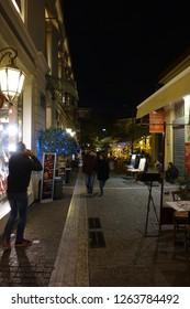 Monastiraki, Athens / Greece: December 20 2018: Night shot from famous area of Monastiraki wit festive coffee shops and taverns during Christmas time