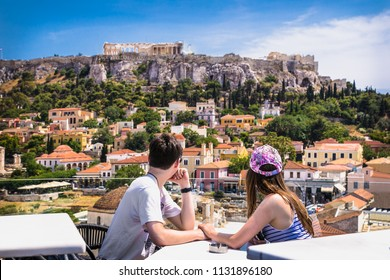 MONASTIRAKI ATHENS GREECE, JUN 11 2016: Young couple at caffe on Monastiraki square and Acropolis view on Jun 11, 2016 in  Athens ,Greece.