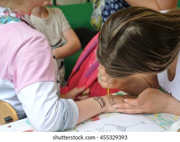 "MONCHEGORSK, RUSSIA - JULY 2016: Professional holiday ""Day of Metallurgist"" in city park. lass volunteer project ""Good Works"" makes temporary tattoos on the girl's wrist ornament"