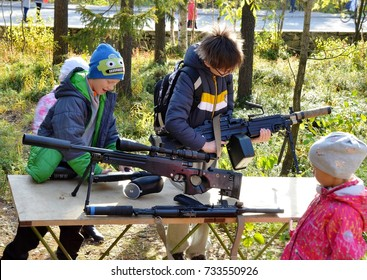 MONCHEGORSK, RUSSIA - SEPTEMBER 23, 2017: Two teenage boys are enthusiastically looking at laser paintball guns. City park, outdoor entertainment, a holiday in honor of the town's anniversary