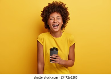 Monchrome shot of cheerful dark skinned woman laughs and talks casually, holds disposable cup of tea, wears yellow bright t shirt. Curly Afro American girl enjoys hot chocolate. Lifestyle concept