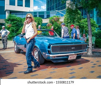 Moncton, New Brunswick, Canada - July 11, 2014: A lady steps in front of a 1968 Chevy Camaro SS convertible parked in the downtown area of Moncton during the 2014 Atlantic Nationals.