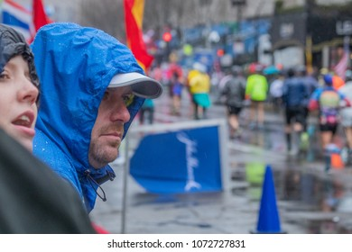 Monday, April 16 (Boston Massachusets) A spectator in blue rain poncho and a young girl are watching runners at the 122nd Boston Marathon.