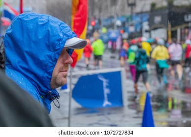 Monday, April 16 (Boston Massachusets) A spectator in blue rain poncho is watching runners at the 122nd Boston Marathon.