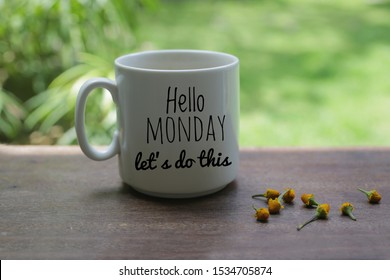 Monday motivational greeting & notes on white mug of coffee - Hello Monday, lets do this. With little yellow flowers arrangement on wooden table and light green garden bokeh background.