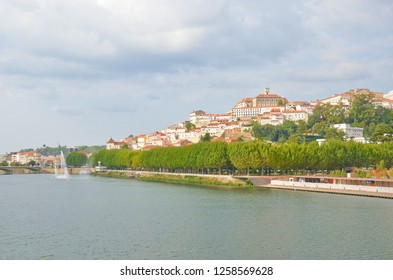 Mondego River along the Coimbra city in Portugal on a cloudy summer day. The most significant sight of the city is famous University of Coimbra with dominant bell tower. Sep 4th 2018