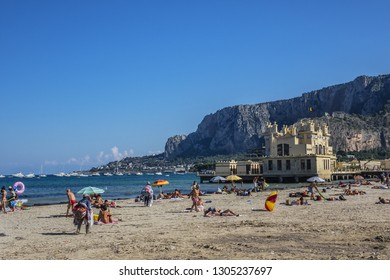 MONDELLO, SICILY, ITALY - SEPTEMBER 30, 2018: People swimming in sea and relaxing on Mondello Beach. Mondello Beach - historic seaside resort with white sandy beach, spanning more than 1,5 kilometers.