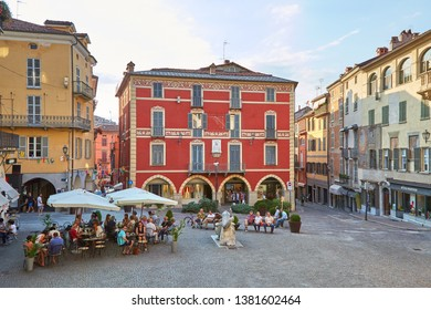 MONDOVI, ITALY - AUGUST 15, 2016: Moro square with people sitting at sidewalk tables in a sunny summer day, blue sky in Mondovi, Italy.