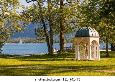 Mondsee, Austria - May 28, 2017:  Seepromenade park near Mondsee lake with green lawns, a small chapel and a beautiful view of the lake.