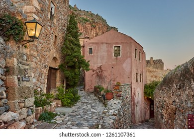 MONEMVASIA, LACONIA, GREECE - DECEMBER 2018: Stone alley into the picturesque castle town of Monemvasia during winter. Architectural stone buildings and beautiful narrow paved streets in Monemvasia.